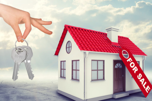 House for sale with hand holding keys on blue sky background